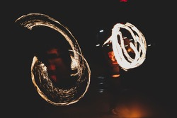 Street performers hold a fire show at night
