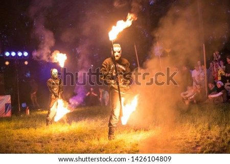 Street performers hold a fire show with fireworks at night #1426104809