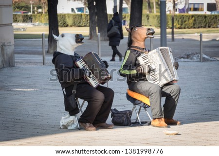 Street performers play on accordion in horse masks. Outdoor show. Vienna, Austria. #1381998776