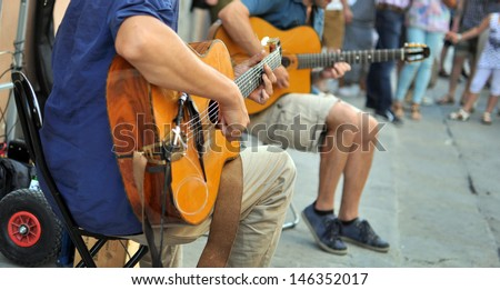 street performers with guitar, with audience in the background