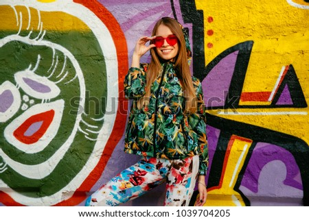 Stock Photo Street photo of beautiful girl in red eyeglasses. Dressed up in green colorful jacket, and pants. Standing on the background with graffiti.