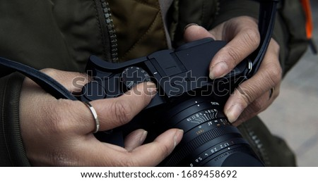Street photographer adjusts settings on her manual camera changing the focus while shooting from the hip