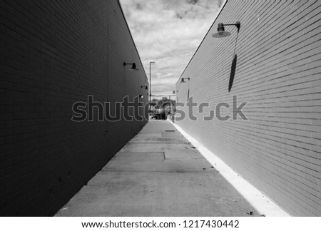 Street photography of abstract long alleyway. Pathway between two buildings with red brick wall facade. Minimal street photography. Light and shadow on brick wall exteriors.