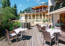 Street restaurant with tables and chairs at hotel resort in Bad Kleinkirchheim in Carinthia, Austria. Design of Sidewalk cafe. Lifestyle and nature. Terrace or veranda of cafe ready for breakfast