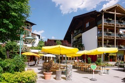 Street restaurant with umbrellas, tables and chairs at hotel and family resort in Bad Kleinkirchheim in Carinthia, Austria. Sidewalk cafe terrace and building architecture with outdoor. Lifestyle.