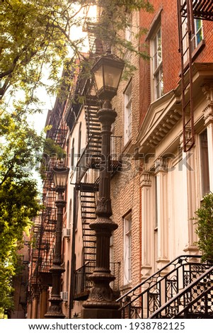 Street scene of residential neighborhood with a row of buildings seen from New York City Manhattan