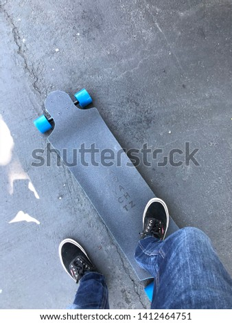 Street scene with skateboard and person looking down on skateboard and street. Colors capture a cool blue, black and charcoal grey. #1412464751