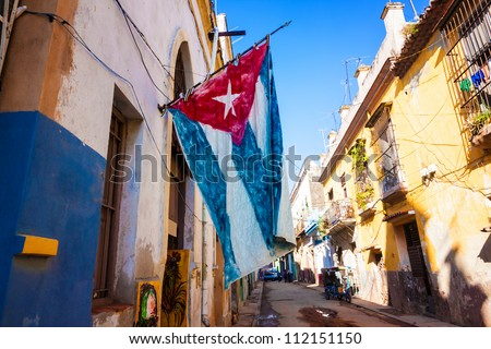 Shutterstock Street  sidelined by decaying buildings in Old Havana with a big cuban flag