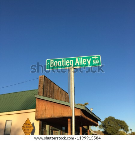 Street sign for Bootleg Alley in front of old false front building