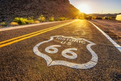 Street sign on historic route 66 in the Mojave desert photographed against the sun at sunset