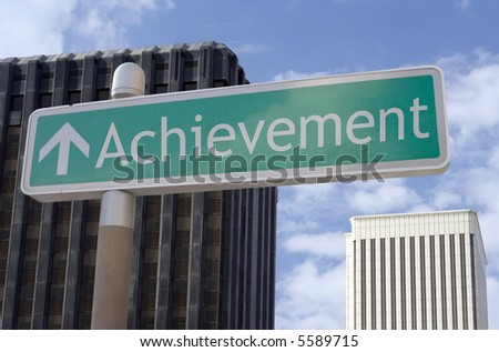 """Street sign with an arrow and the word """"achievement"""" located in a business district."""