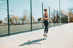 Street sport. The girl jumps on a skipping rope. Athletic girl in a sports uniform.