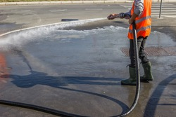 Street sprayed clean with pressurized water, wet cleaning of street. Selective focus.