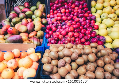 Street stall selling tropical fruits, faded colors.