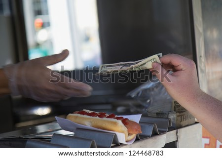 Street stall to sell hot dogs. Paying for purchased hot dog. (New York City, USA)