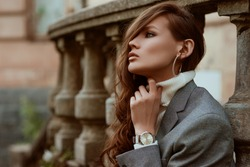 Street style autumn portrait of elegant fashionable woman wearing trendy silver wrist watch, checkered blazer, white turtleneck, hoop earrings, posing outdoors, in city. Copy, empty space for text