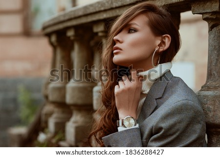 Street style autumn portrait of elegant fashionable woman wearing trendy silver wrist watch, checkered blazer, white turtleneck, hoop earrings, posing outdoors, in city. Copy, empty space for text Stock photo ©