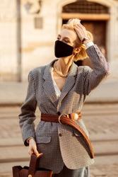 Street style during quarantine: elegant blonde woman wearing black protective face mask, trendy autumn blazer, wide brown wicker belt, wrist watch, walking in street of European city