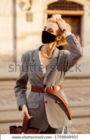 Street style during quarantine: elegant blonde woman wearing black protective face mask, trendy autumn blazer, wide brown wicker belt, wrist watch, walking in street of European city Сток-фото ©