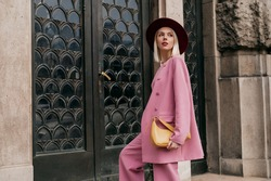 Street style, fashion conception: elegant woman wearing trendy pink suit, burgundy color hat, holding yellow bag, posing in street of city. Copy, empty space for text