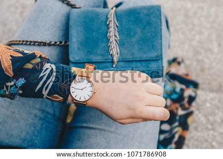 Photo of  street style fashion details. close up, young fashion blogger wearing a floral jacker, and a white and golden analog wrist watch. checking the time, holding a beautiful suede leather purse.