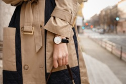 street style fashion details. close up, young fashion blogger wearing autumn trench coat and a white and golden black analog wrist watch. checking the time, holding a beautiful brown leather purse.