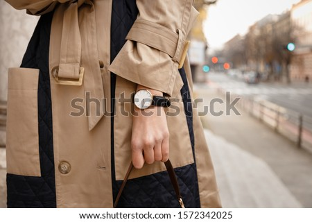 street style fashion details. close up, young fashion blogger wearing autumn trench coat and a white and golden black analog wrist watch. checking the time, holding a beautiful brown leather purse.  Stock photo ©