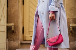 Street style, fashion details: small pink faux patent leather baguette bag in trendy outfit. Woman holding mini handbag. Copy, empty space for text