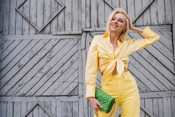 Street style, fashion portrait of happy smiling fashionable woman wearing  total yellow outfit: shirt, jeans, holding trendy quilted green faux leather bag. Copy, empty space for text