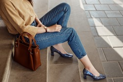 Street style, fashion trends concept: crop of fashionable woman`s outfit. Lady wearing casual clothes, python print, textured shoes with square toe, block heels. Copy, empty space for text