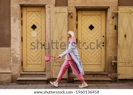 Street style, fashion: woman wearing  trendy sport chic outfit walking in street of European city. Blue trench coat, sunglasses, pink hoodie, trousers, sneakers, mini bag. Copy, empty space for text