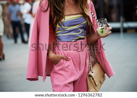 Street style image of young woman wearing pink suit with high waisted belt, holding a cocktail, mid section, horizontal