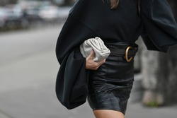 Street style outfit – Woman wearing a black oversized sweater and leather skirt matched with a clutch bag – StreetStyleFW2020