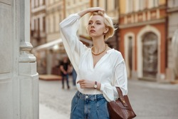 Street style photo of elegant fashionable woman wearing trendy white blouse, high waist jeans, wrist watch, with brown faux croco leather textured bag. Model walking in street of European city