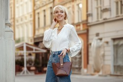 Street style photo of happy smiling fashionable woman wearing trendy white blouse, high waist jeans, holding brown faux croco leather textured bag. Model posing in street of European city. Copy space