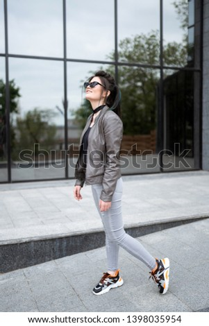 Street style photosession. Beautiful asian girl standing near modern house. Not looking in camera. Looking on the sun. #1398035954