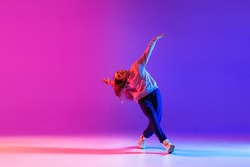 Street style. Young beautiful female hip-hop dancer dancing isolated on neon studio background. Sport achievement, spirit of expression. Concept of dance, youth, hobby, dynamics, movement, action, ad