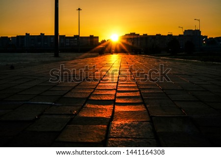 Street tiles in europe and people walking.Cobbles at sunset. Sunlight on Cobbled Stones against russian houses. sun light and sun rays. full building background.