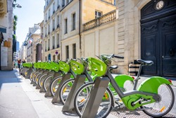 Street transportation green public rent bicycles with basket for traveling around the Paris city stand in row on rental network parking lot waiting for cyclists ready to make an exciting bike trip