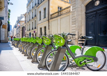 Street transportation green public rent bicycles with basket for traveling around the Paris city stand in row on rental network parking lot waiting for cyclists ready to make an exciting bike trip stock photo