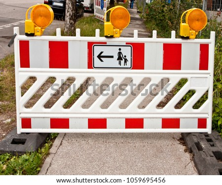 Street under construction,  boundary road fence with sign of no footway, deviation for pedestrian passage with flashing lights #1059695456