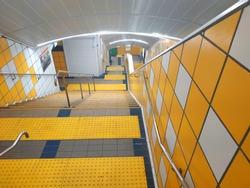 Street urban staircase with yellow illumination leading underground. Subway