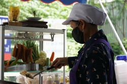 Street vendor Asian woman wears face mask, keeps social distancing for safe travels, prevents covid-19 while selling street local food at sidewalk. Concept new normal.