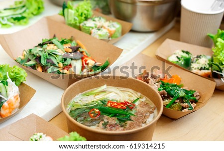 Street vendor's vegetable salads sold outdoors. Snacks closeup, in craft package. Fast food for commercial kitchen. #619314215