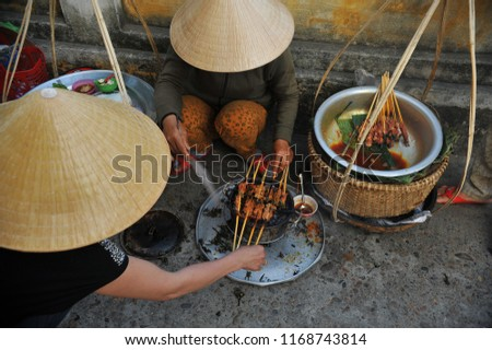 Street vendor with conical head prepare roasted skewers on charcoal fire.  Sidewalk barbeque is one of popular tourist attraction in Hoi An, Vietnam.