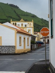 Street view in Santa Cruz das Flores with the Convent of São Boaventura in the background, contrasting with the green of the mountain behind it. Flores Island.