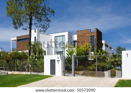 Street view of a beautiful villa with a healthy garden on a sunny day
