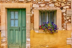 Street view of a picturesque house facade in Provence, where a layer of locally mined ochre has been partially removed, revealing a stone wall underneath. Roussillon, France.