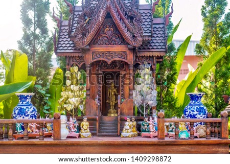 Street view of an ornate Thai spirit house, a miniature replica of a traditional style home, where a deity is believed to live as spiritual guardian of the property and offerings made.