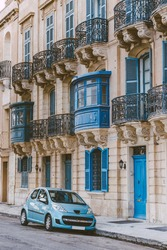 Street view of blue car in front of traditional Maltese house with blue covered balconies in historical part of the old town of Valletta in Malta. Vintage picturesque tourist postcard.